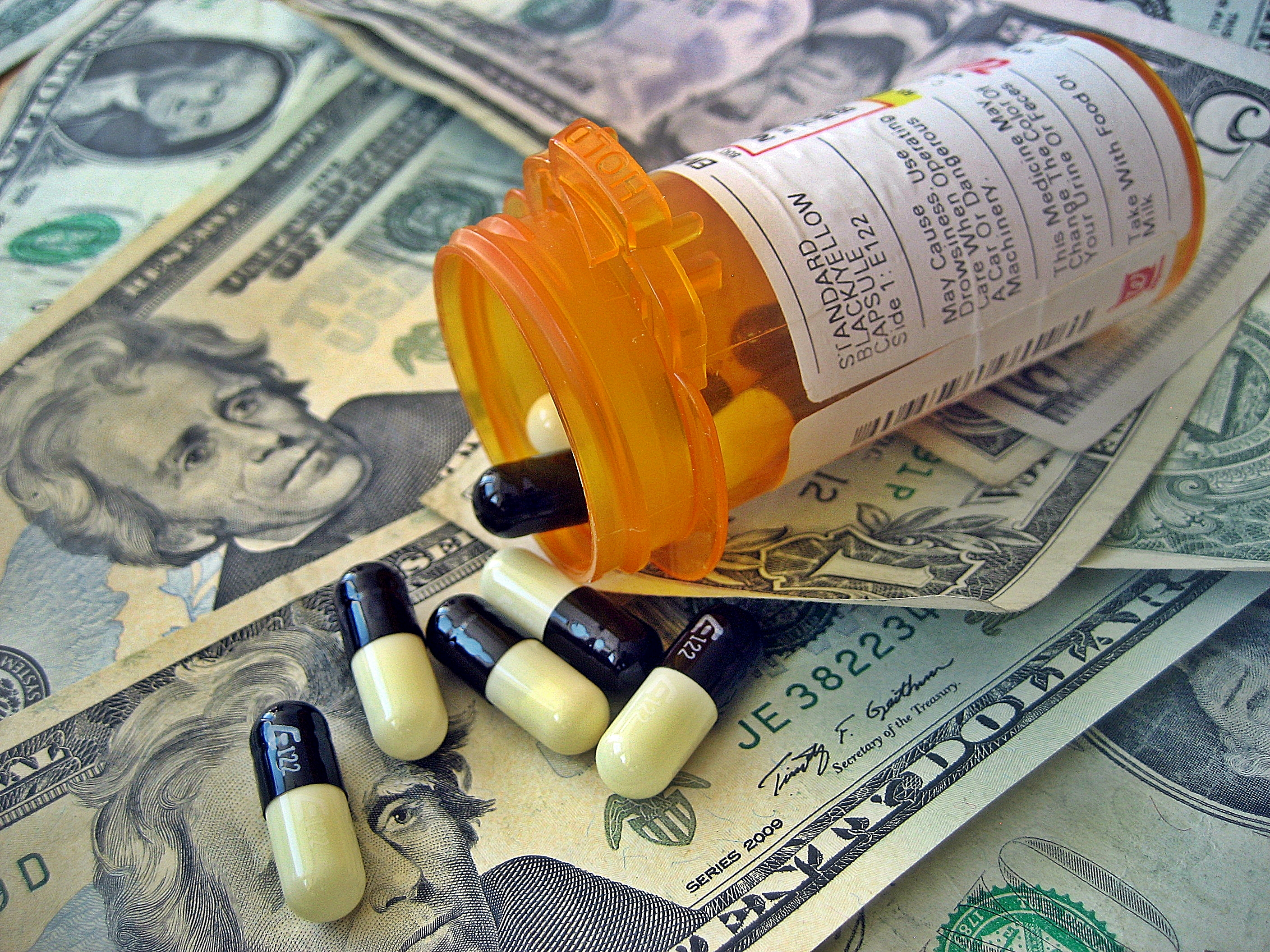 Pills and cash; photo by Tax Rebate UK via Flickr.