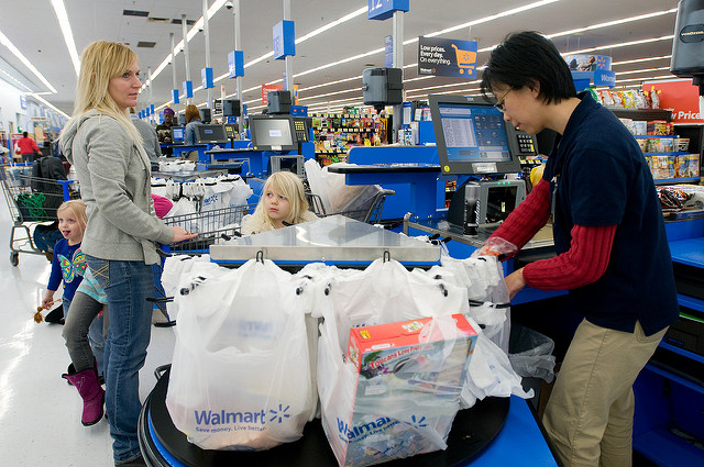 Cashier bags up a grocery purchases at a Gladstone, Mo. Walmart. Photo by Walmart via Flickr.