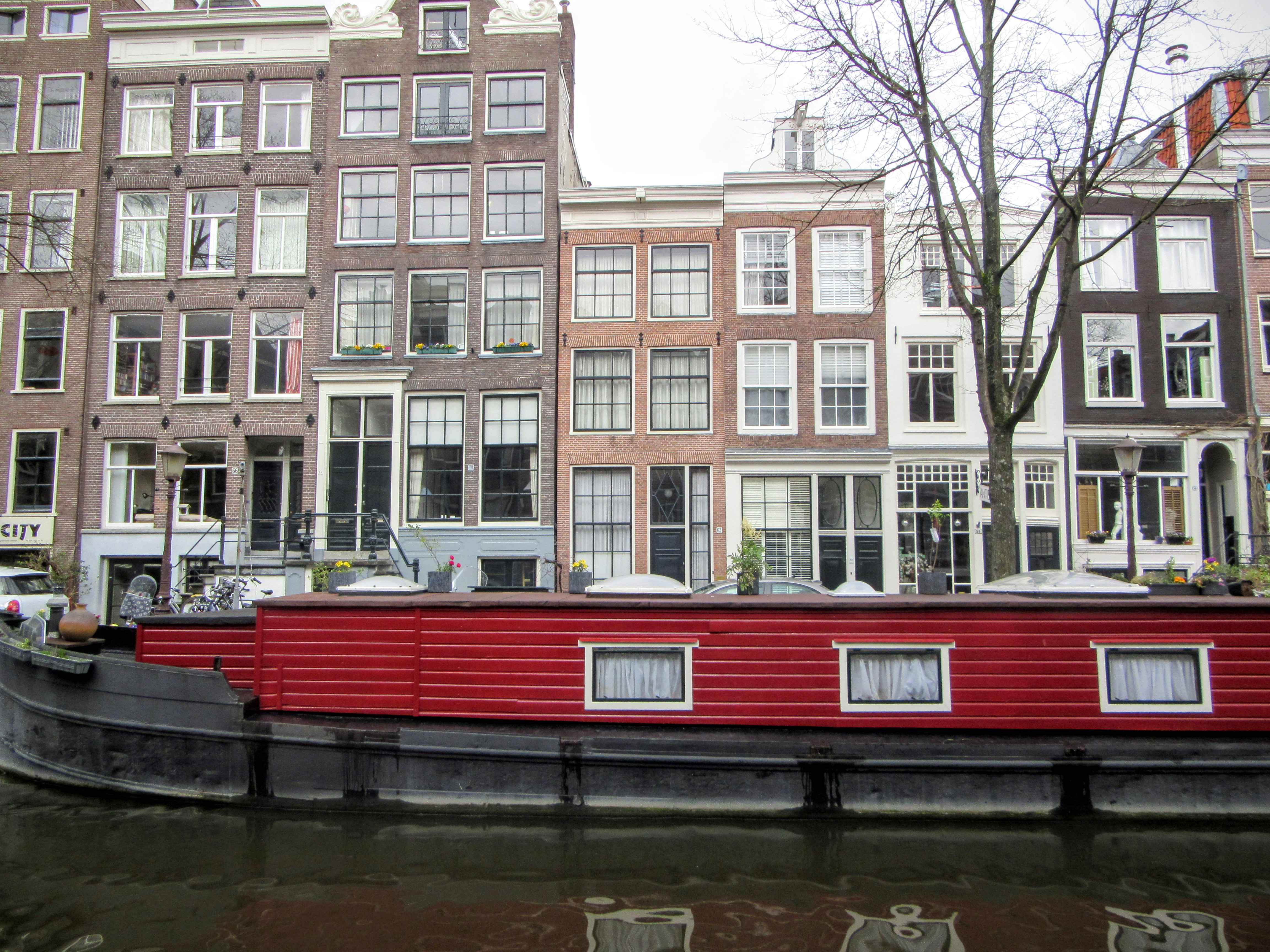 A house boat and homes along canal in Amsterdam. | On Traveling Europe Together.